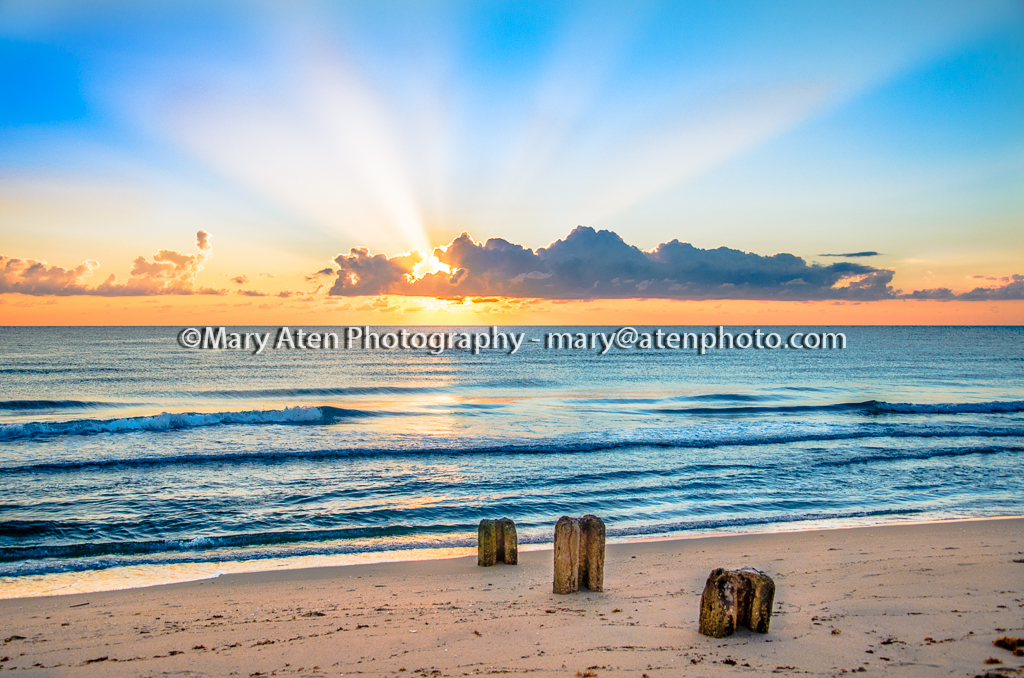 Sunset Photo With Sun Rays And Pilings On Beach Mary